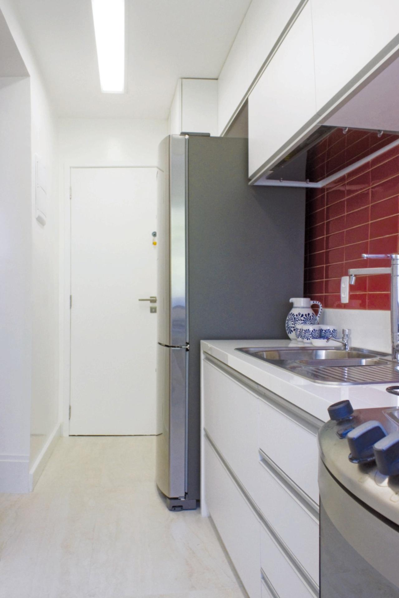 Estreita e pequena, a cozinha tem os eletrodomésticos distribuídos em uma das paredes para aproveitar melhor o espaço para a circulação. Na área molhada (à dir.), a parede foi revestida com cerâmica modelo Liverpool, da Portobello. A bancada estruturada pela superfície de vidro cristalizada é combinada à marcenaria. A reforma no apê em Botafogo, Rio de Janeiro, tem assinatura dos arquitetos do escritório Ravaglia & Philot