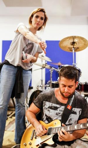 Tatá faz sinal de negativo para o solo de guitarra de Maurício Meirelles durante o ensaio da banda