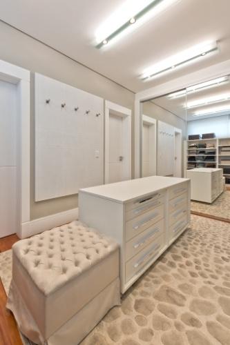 O closet aberto para a suíte máster da casa Alphaville tem móveis planejados (Florence) com portas espelhadas. A decoração assinada pela arquiteta Carla Kiss leva papel de parede e tapetes em tons de palha
