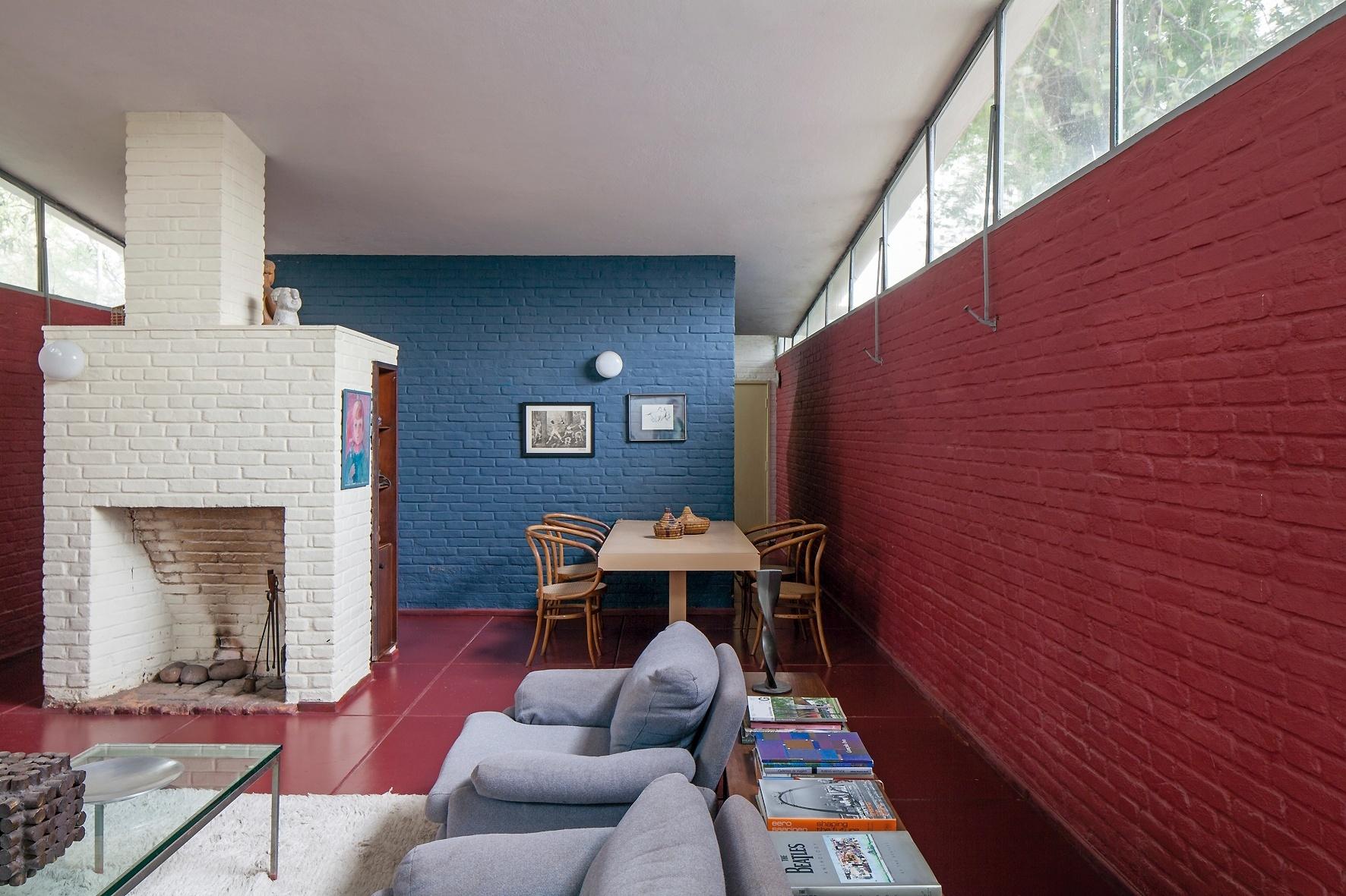 A lareira com tijolos aparentes, pintados de branco, dá aconchego às salas de jantar e estar. A face oposta foi aproveitada para a instalação de um armário. A Casa do Arquiteto foi projetada por João Batista Vilanova Artigas (1915-1985), em 1949