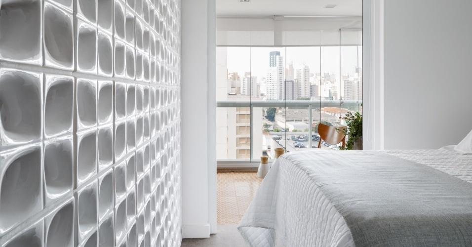Com a reforma projetada pela arquiteta Marcela Madureira, a parede convencional que separava o dormitório do casal da sala de estar foi substituída a uma outra, composta de elementos vazados brancos (cobogós). A solução define ao passo que interliga os espaços do apê com menos de 40 m²