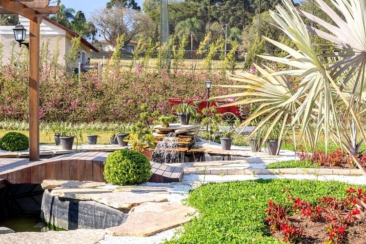 Um lago com carpas e cascata proporciona descanso e contemplação no jardim da chácara em Araucária, no Paraná. O espaço dispõe ainda de um deck de itaúba protegido por um pergolado de cumaru. Ao fundo, canteiros de azaléias, marias-sem-vergonha e corações-roxos. O projeto de arquitetura e paisagismo é assinado por Juliana Lahóz