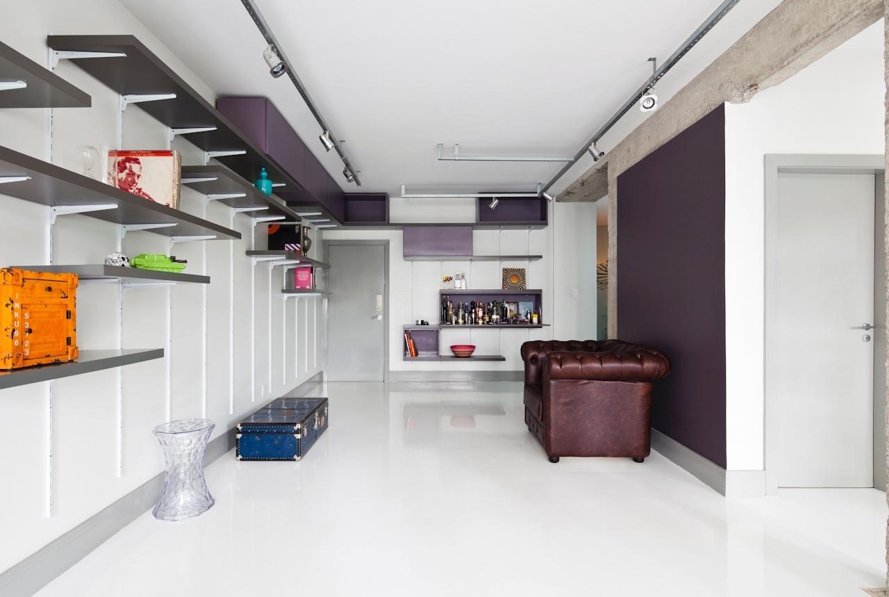 A marcenaria laqueada da sala de estar do apartamento Perdizes é simples, original e inteligente: prateleiras e nichos são encaixados no sistema de cremalheiras, que permite a movimentação vertical dos módulos, flexibilizando o