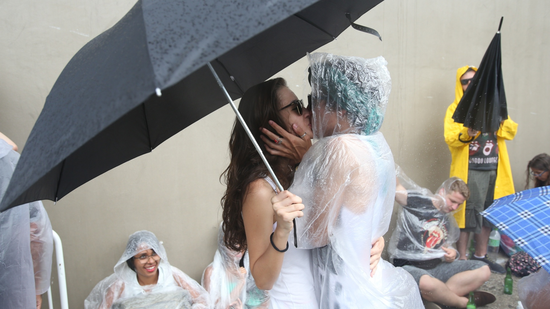 24.fev.2016 - Fãs se beijam debaixo de chuva antes de entrar no estádio do Morumbi para assistir ao primeiro show da