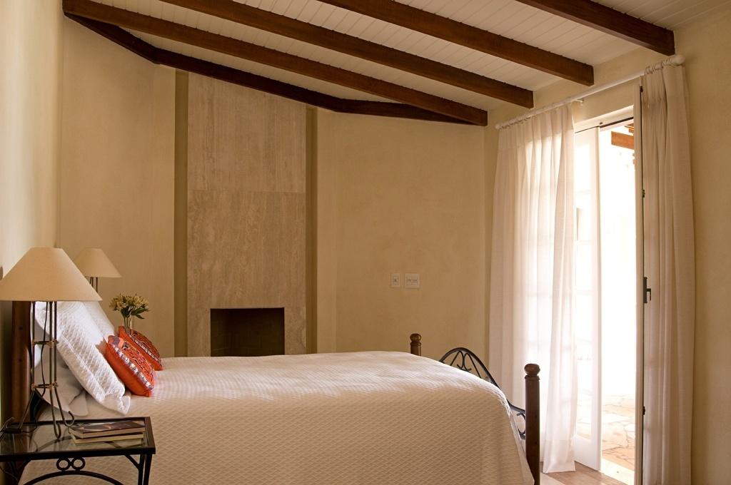 decoracao de interiores de casas de madeira:Neste quarto de casal de uma casa de campo, a lareira (ao fundo