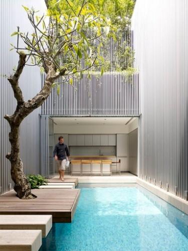 Na proposta arquitetônica do escritório ONG&ONG, a árvore pré-existente no terreno fazia parte do jardim de uma antiga construção na Malásia. O exemplar foi mantido e faz parte da nova área de lazer graças ao deck de madeira, instalado em torno da planta
