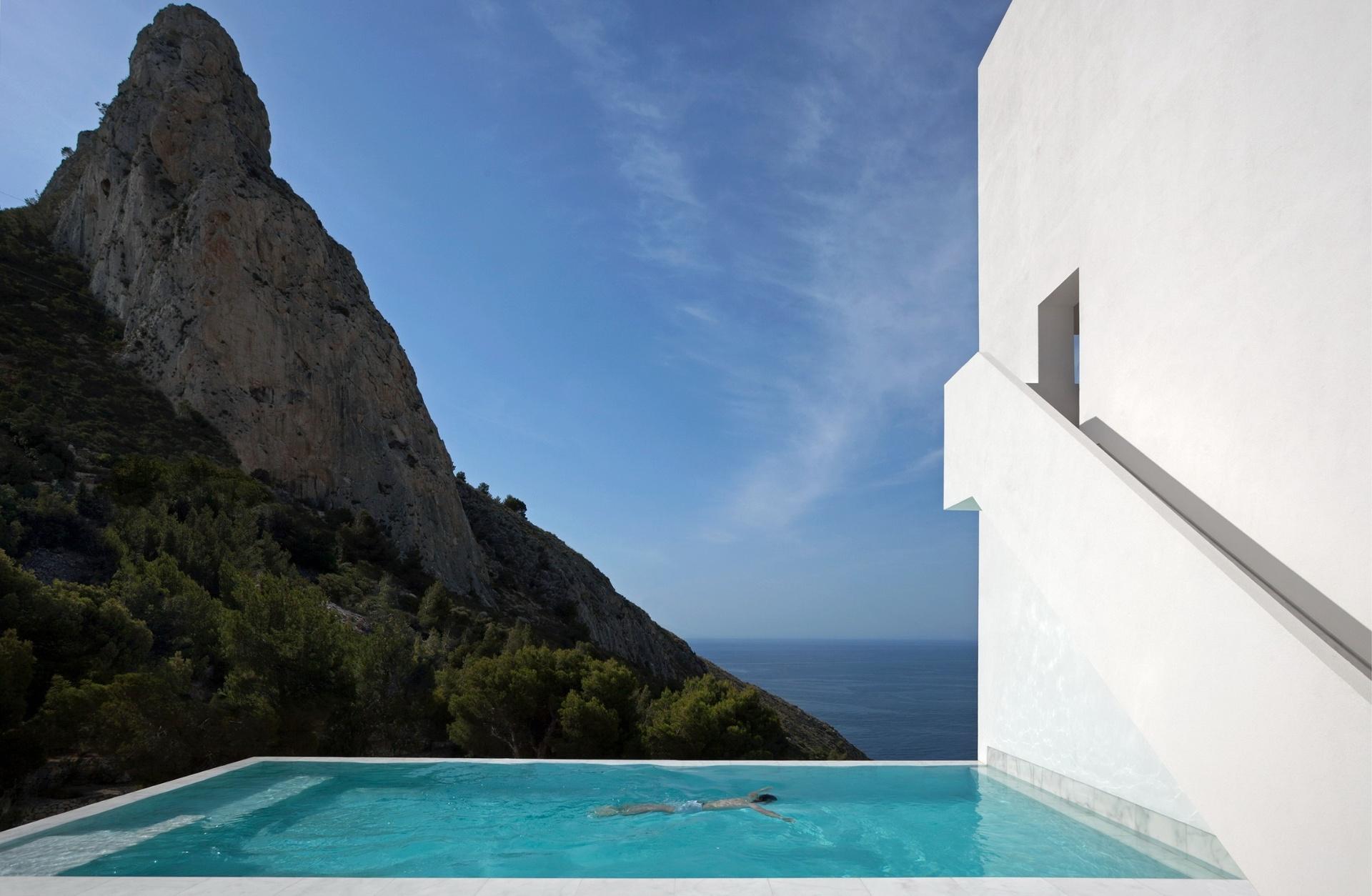 Para acentuar a ideia de integração entre a residência e a paisagem e trazer o mar para perto da Casa do Penhasco, os arquitetos do escritório Fran Silvestre projetaram uma piscina com borda infinita em Calpe, Alicante, no litoral da Espanha