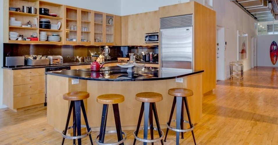 A cozinha do loft de Adam Levine e Behati Prinsloo tem acabamento em madeira com brilho suave, inclusive na ilha de cocção com tampo de granito preto e cooktop. A geladeira (à dir.), assim como outros eletrodomésticos, fica embutida. O loft do vocalista do Maroon 5 e da modelo da Victoria's Secret está à venda por cerca de R$ 20 milhões, em Nova York, Estados Unidos