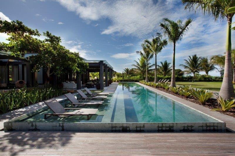 Para a área de lazer da casa Areia, a arquiteta Debora Aguiar projetou uma piscina em L, revestida em pedras Hijau (Palimanan) e acompanhada por uma fileira de palmeiras e bromélias. As espreguiçadeiras são da Franccino e ficam na prainha