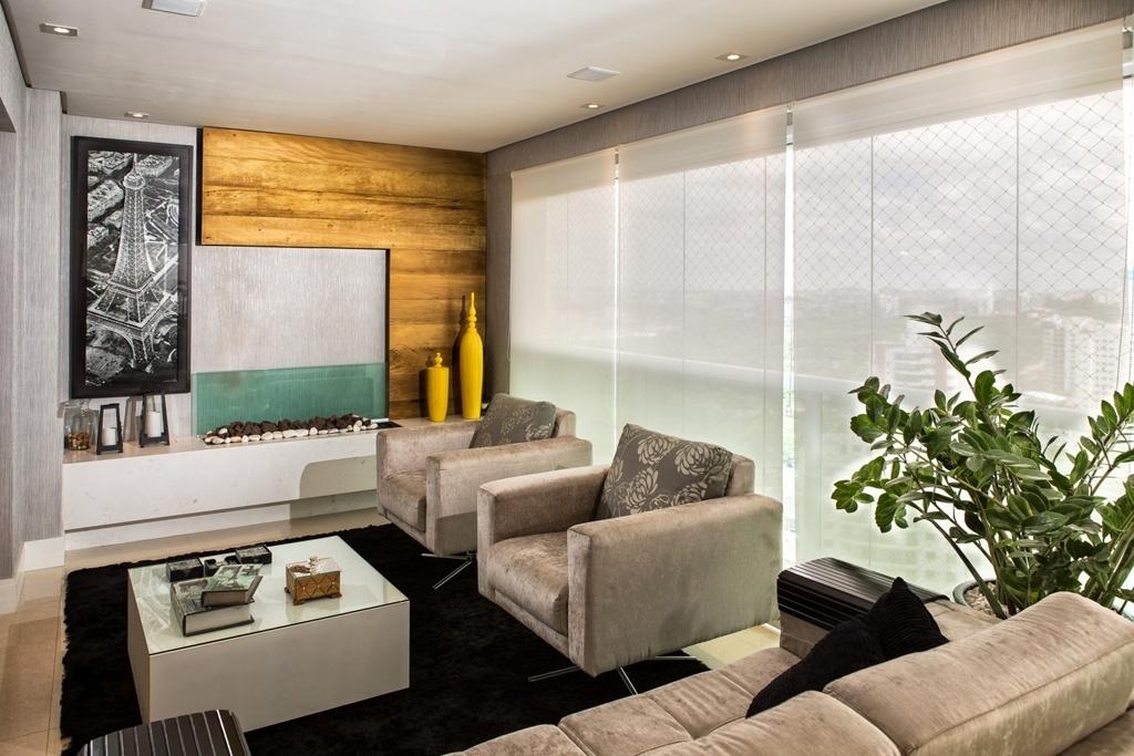 No projeto da designer de interiores Dinna Albuquerque, a sala de TV está adequada ao inverno: os estofados são revestidos com veludo, o tapete é felpudo e há uma lareira. O painel em madeira também aquece o ambiente, que foi revestido por um tipo de papel de parede que, promete a fabricante, isola termicamente o espaço
