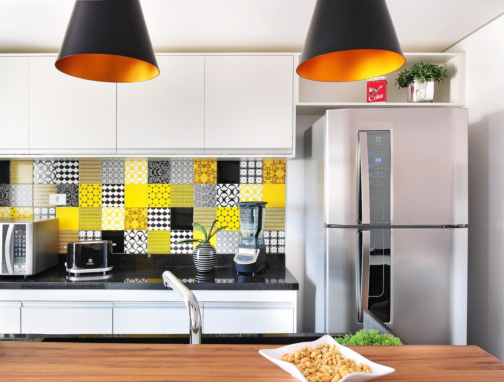 O grande destaque da proposta do IBD Arquitetura e Interiores para o apartamento Patch 01 é o revestimento da parede da cozinha feito com os azulejos (Pavão Revestimentos) com padronagens diversas, mas sempre em amarelo e preto. A partir dessa composição, todo projeto de design foi desenvolvido. À direita, a geladeira metálica dá o tom de modernidade ao imóvel na Cantareira, em São Paulo