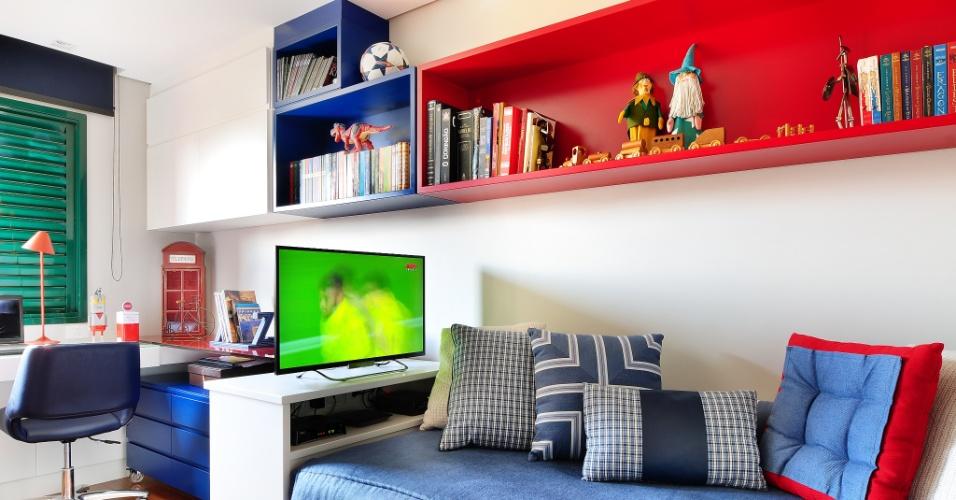 No quarto do adolescente, com dimensões enxutas (10 m²), as cores predominantes são o azul e o vermelho. A janela de alumínio do apê Jardim Marajoara foi pintada de verde, enquanto a persiana (Uniflex) azul acompanha a poltrona de couro. Até a roupa de cama e as almofadas (Entreposto) seguem o padrão de cores especificado pela arquiteta Ana Yoshida