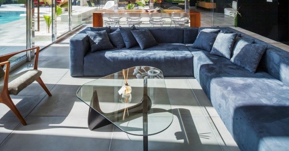 Na área interna de convivência (estar e jantar), o piso é o mesmo da área externa: um cimentício atérmico (Solarium). O elemento aponta a continuidade entre áreas interna e externa e combina com os elementos estruturais (laje e pilares), mantidos em concreto aparente e finalizados com verniz. Da mobília destacam-se a mesa de centro Noguchi, o par de cadeiras Vladimir Kagan (à esq.) e o sofá da Tapeçaria Juca. A casa Botucatu tem projeto do escritório paulistano FGMF Arquitetos