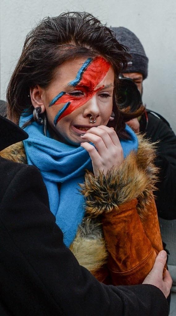 11.jan.2015 - Mulher chora pela morte de David Bowie após deixar flores em frente a um mural do cantor em Brixton, no sul de Londres