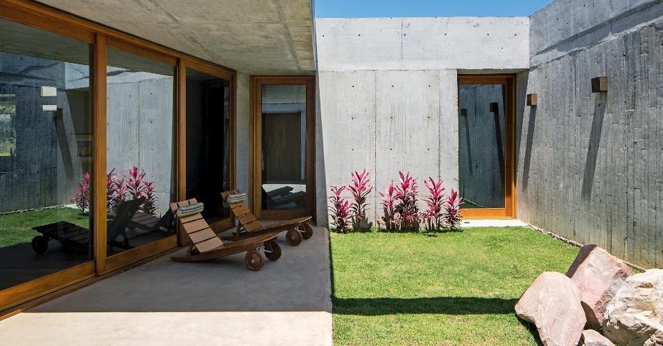 A sala de estar, à esquerda, está voltada para um pátio interno ajardinado, equipado com espreguiçadeiras. A Casa do Bomba, uma morada de veraneio na Chapada Diamantina (BA), foi projetada pelo escritório Sotero Arquitetos
