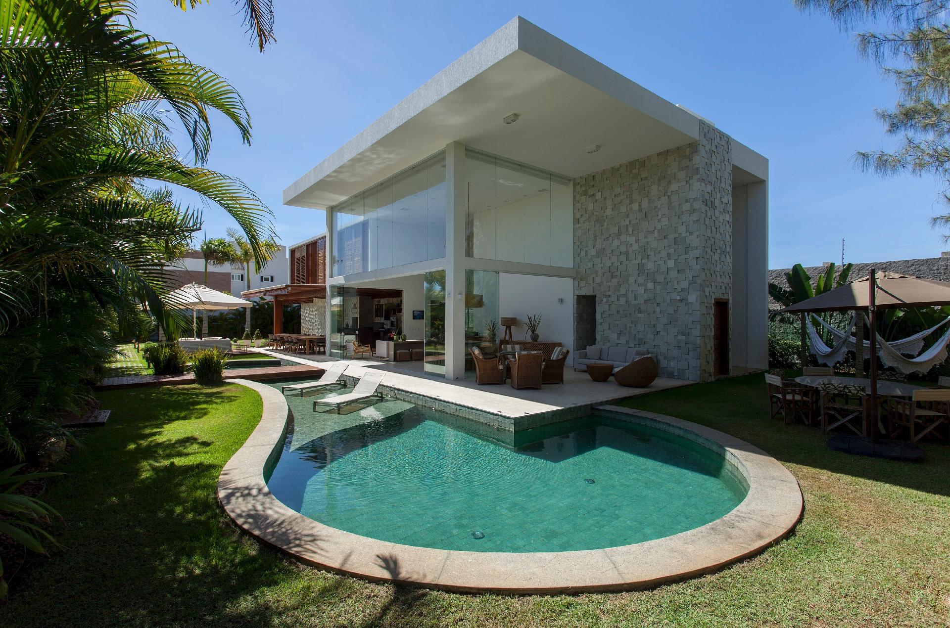 A piscina é revestida em pedra hijau verde de origem vulcânica. Ao lado, uma mesa com guarda-sol do tipo ombrelone e redes completam o ambiente. O projeto de arquitetura e interiores é do escritório SQ+ Arquitetos Associados