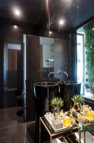 O lavabo em granito preto absoluto reflete a sofisticação da residência em Salvador (BA), idealizada por Sidney Quintela do SQ+ Arquitetos Associados. O pano de vidro integra o espaço ao jardim externo