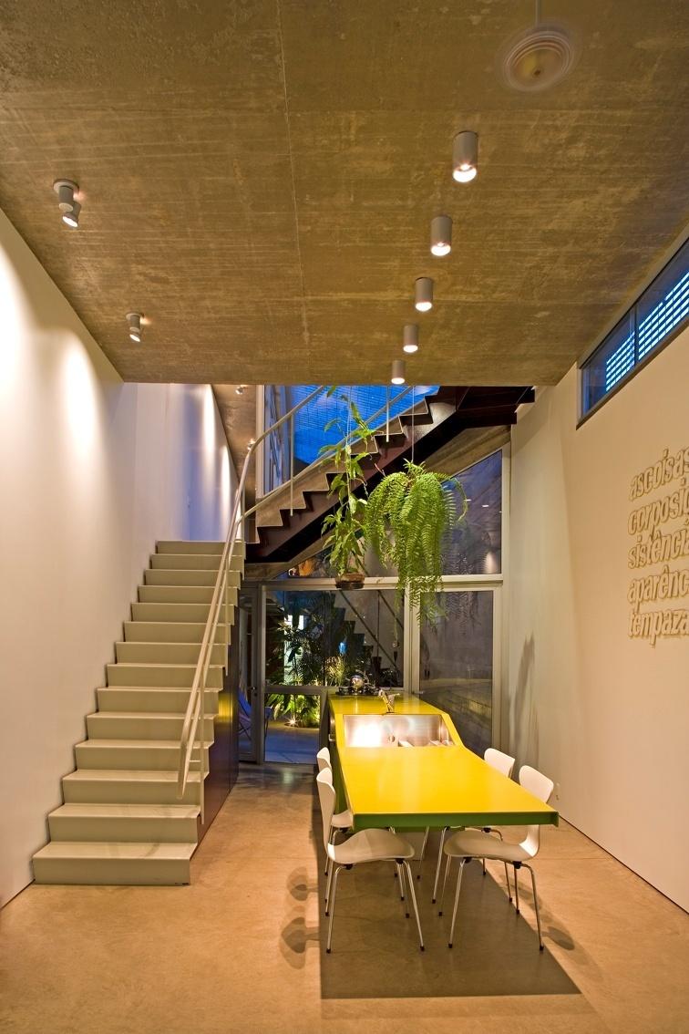 O living com cozinha integrada (foto) tem continuidade com o pátio interno (corredor-jardim). Linear, a área ajardinada é antecedida por uma fachada de vidro e pela bancada com sete metros de extensão. A ideia dos arquitetos do escritório Procter-Rihl era dar profundidade ao espaço estreito de geometria distorcida, com paredes e forros inclinados