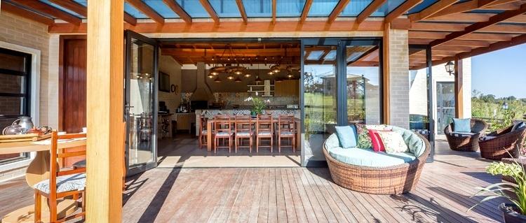A grande varanda desta casa no Paraná, apresenta deck de madeira itaúba e pergolado de cumaru. Os tijolos ecológicos são combinados às esquadrias pretas envidraçadas no projeto de Juliana Lahóz. As mesas, poltronas e cadeiras que compõem a mobília faziam parte do acervo da família