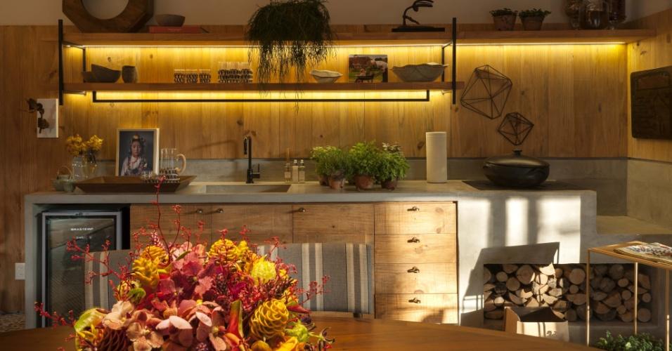 No projeto Casa da Gente, uma criação de Marina Linhares para a edição 2015 da Casa Cor SP, o cimento queimado que dá acabamento ao fogão a lenha, também reveste a bancada da pia. A madeira (pinus) reaproveitada na marcenaria e nos lambris dá ênfase ao clima rústico do espaço