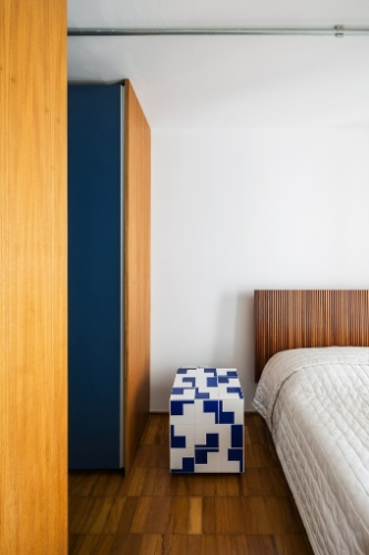 No apê do edifício Gemini, os móveis têm design sofisticado e formas leves. No quarto, o criado-mudo desenhado por Flávio Borsato e Mauricio Lamosa é feito com madeira e conta com acabamento laqueado. O projeto de reforma e a decoração são assinados pelo arquiteto Takuji Nakashima
