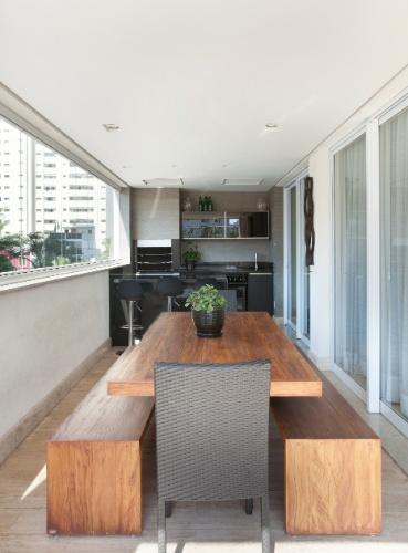 Na estreita varanda gourmet, Raquel Kabbani desenhou uma área compacta para abrigar a churrasqueira. O acabamento preto do móvel planejado contrasta com a mesa de jantar e os bancos em madeira maciça