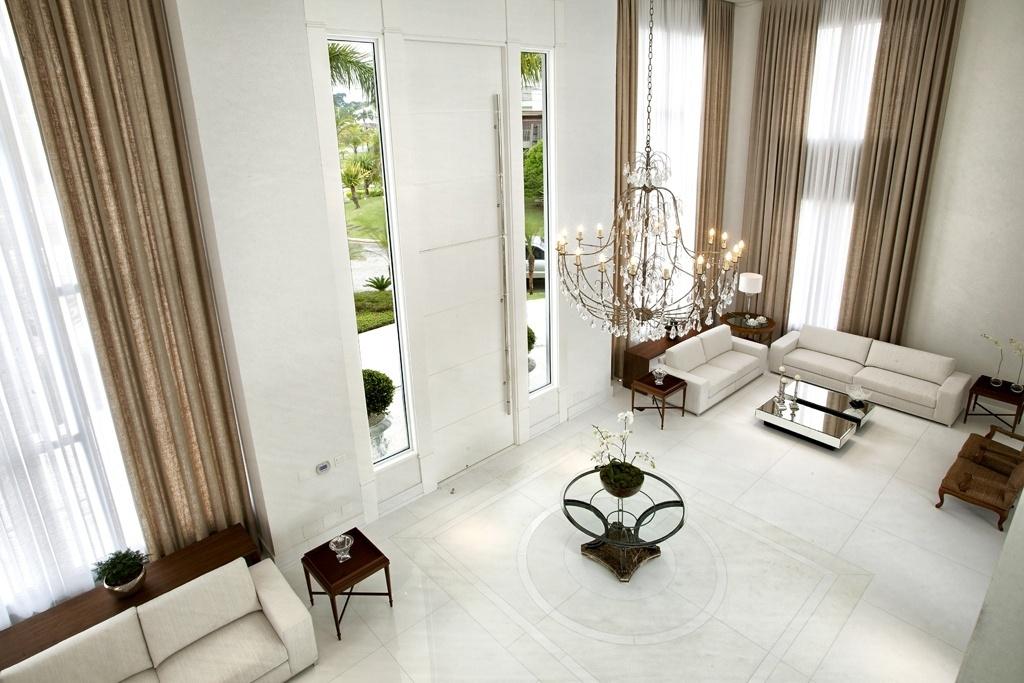 No hall de entrada da Casa Acapulco, com projeto de interiores de Bianka Mugnatto, o piso de Marmoglass branco (liso) tem detalhe central em mármore Thassos. Este ponto divide o ambiente em dois espaços espelhados, porém assimétricos, de estar. A porta de madeira recebeu sete camadas de laca, para resistir à maresia, e mede seis metros de altura, porém, só os três metros inferiores podem ser abertos. Para iluminar naturalmente o ambiente, as janelas generosas são fixas. A casa fica no litoral