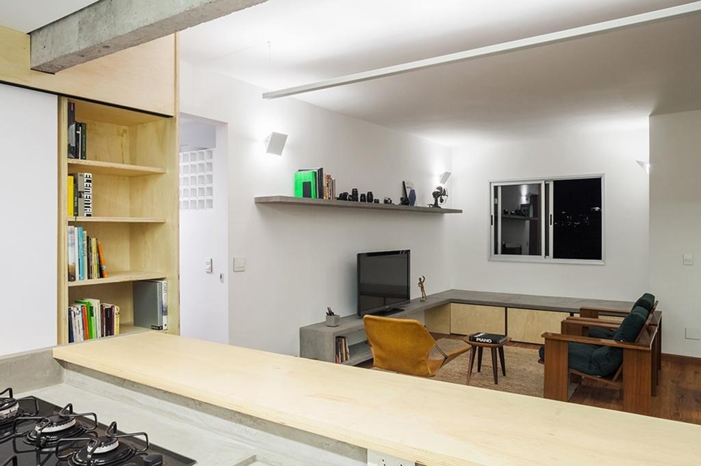 Com a reforma projetada pelo Grupo Garoa Arquitetos no apartamento em São Paulo (SP), a área de estar e a cozinha integram-se pelo balcão desenhado em madeira após a demolição da parede divisória original