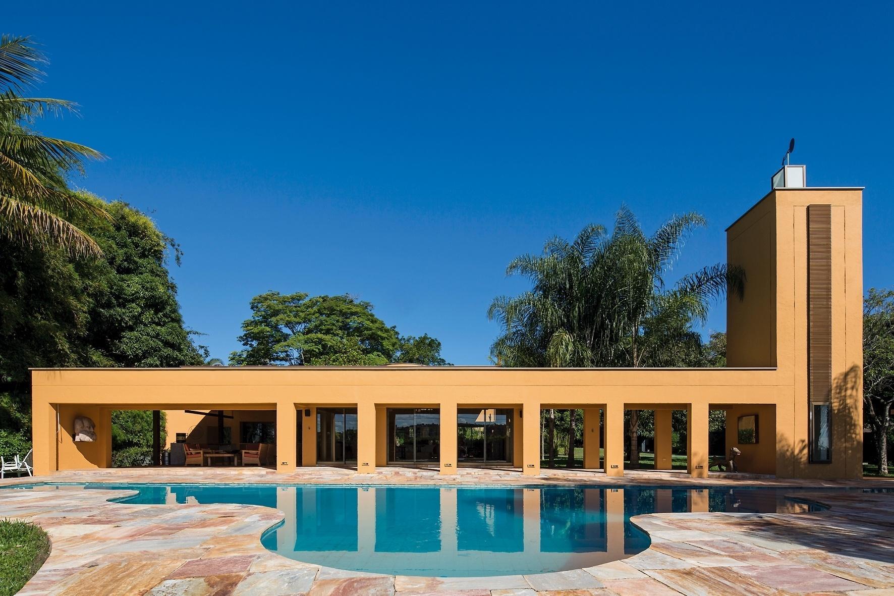 O pórtico de entrada forma um corredor com 12 pilares (seis de cada lado) e desemboca na varanda da casa Várzea, projetada pelo arquiteto Gustavo Penna. À frente da estrutura está a piscina com desenho inusitado, inspirado nas curvas e ondulações das montanhas da região