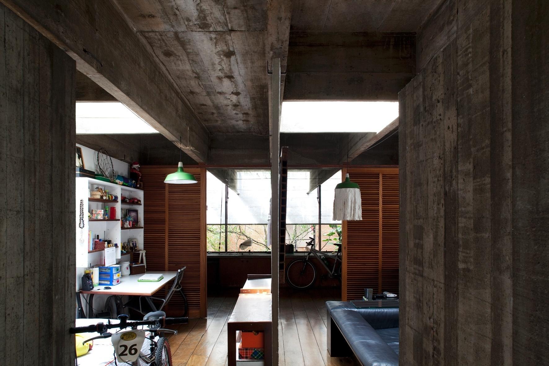 Na foto, é possível ver dois dos cinco dormitórios da casa Butantã, ambos contam com iluminação zenital e têm fechamento com portas-venezianas corrediças. A separação entre os ambientes é tênue e se dá por uma parede de concreto com apenas 3,5 cm de espessura. A residência foi projetada por Paulo Mendes da Rocha nos anos 1960