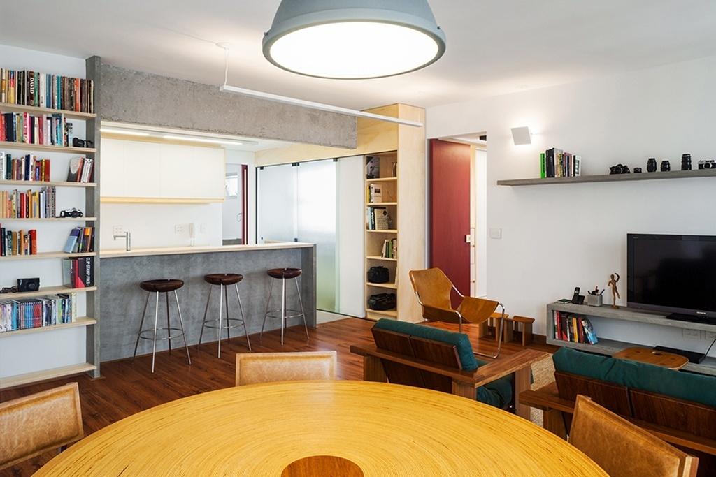 Com a reforma idealizada pelo Grupo Garoa Arquitetos, o apartamento em São Paulo (SP) dos anos 80 ganhou uma grande área social conectada à cozinha, dividida apenas por um balcão de concreto, material que também molda no estar a prateleira e o rack para TV. A iluminação é indireta graças a luz rebatida, oras no teto pela régua, oras na parede por arandelas. Em cima da mesa de jantar, o escritório previu luz direta em uma luminária (Reka) com aparência industrial