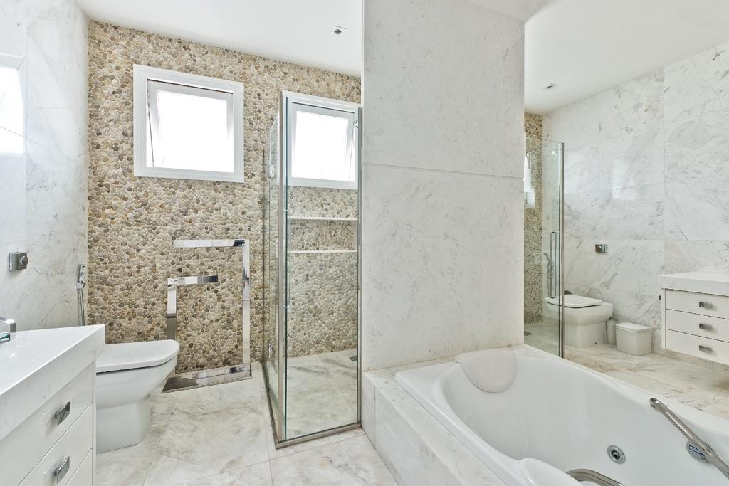 O banheiro da suíte master foi dividido em dois e se divide pelo eixo de hidromassagem e boxes de banho. O espaço é revestido quase totalmente em mármore piguês e tem parede de fundo com mosaico de seixos rolados em vários tons de bege, assinado por Carla Kiss