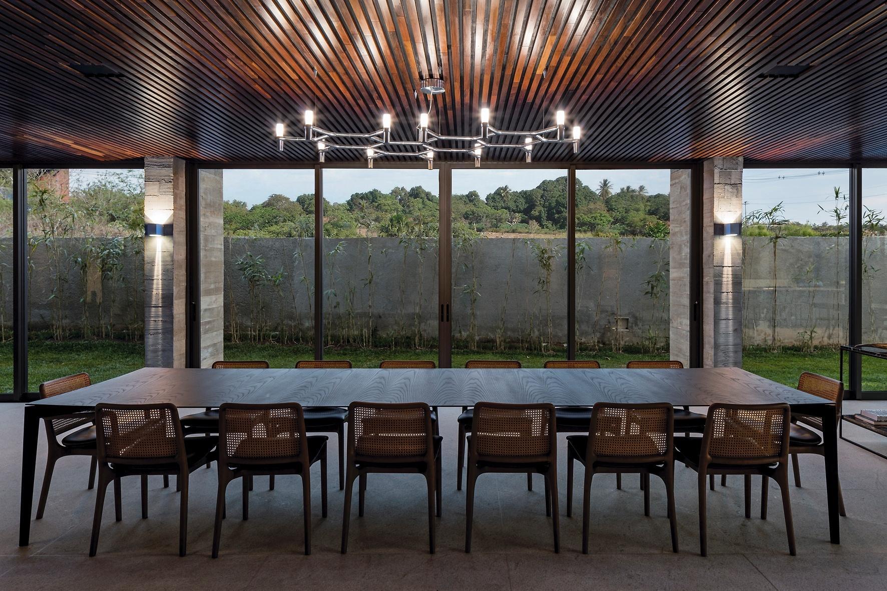 A grande mesa de jantar tem capacidade para reunir 14 pessoas e está voltada para os jardins laterais. O projeto da Casa Braga leva a assinatura do arquiteto Gustavo Penna