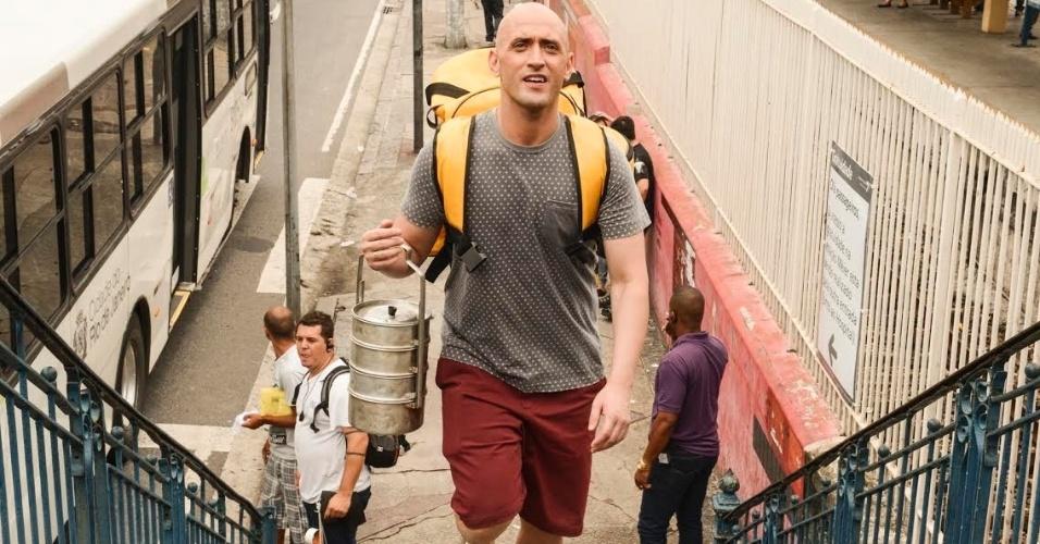 O ator e humorista Paulo Gustavo, no papel de Valdomiro Lacerda, entrega quentinhas no subúrbio do Rio em cena de