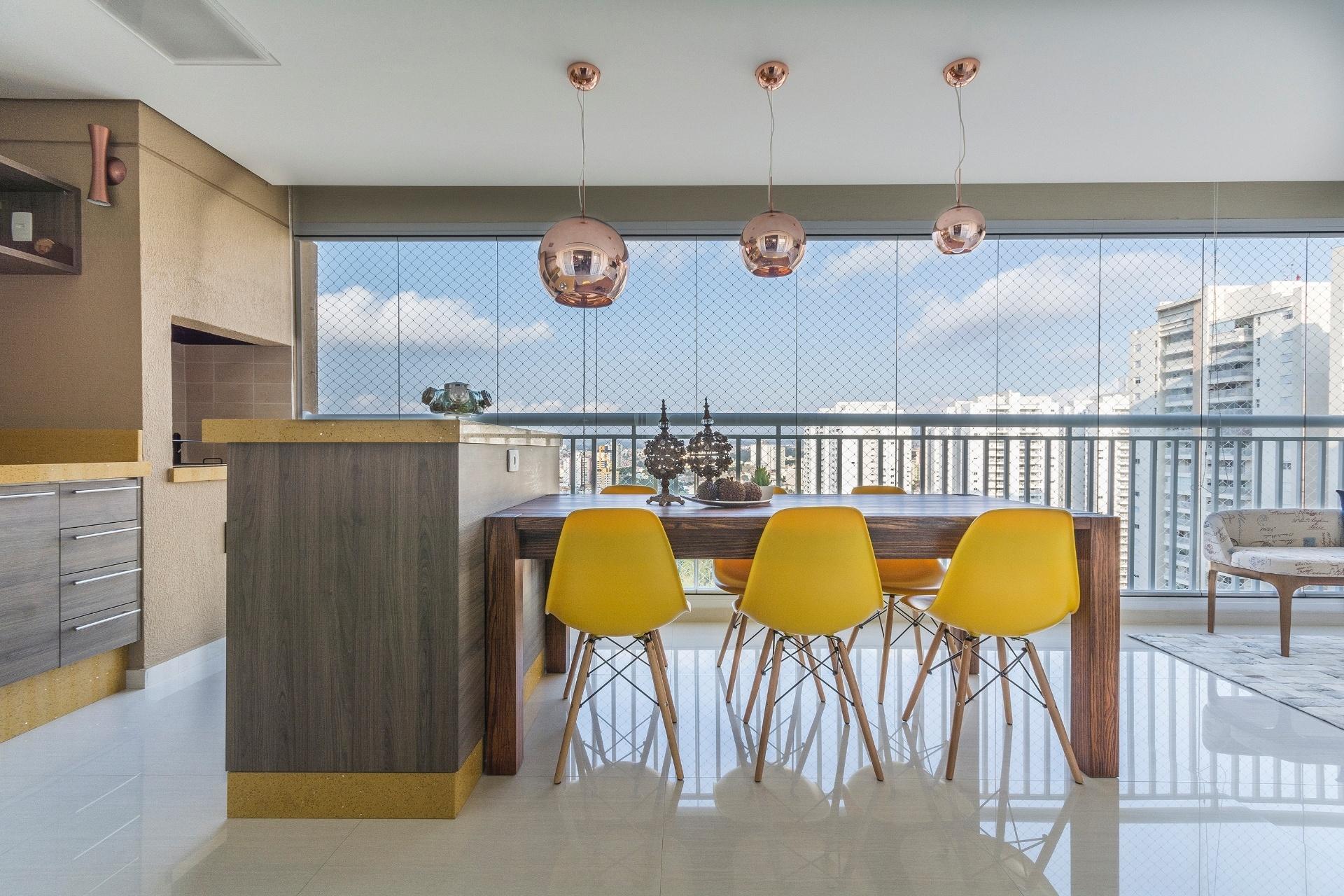 Como esta varanda tem dimensões generosas, a designer de interiores Silvana Borzi empregou uma ampla bancada junto à área da churrasqueira, com mesa de jantar integrada. As cadeiras criadas por Charles e Ray Eames em amarelo e os pendentes de cobre se destacam na decoração neutra