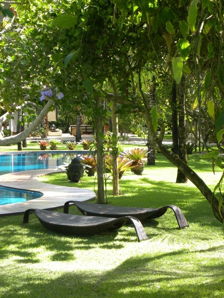 O jardim à beira-mar desta residência em Trancoso, na Bahia, reveste-se de grama esmeralda e une espécies nativas, como cajueiros e licuris às bromélias, que - junto com mobiliário rústico de madeira - compõem o projeto paisagístico criado por Marcelo Faisal
