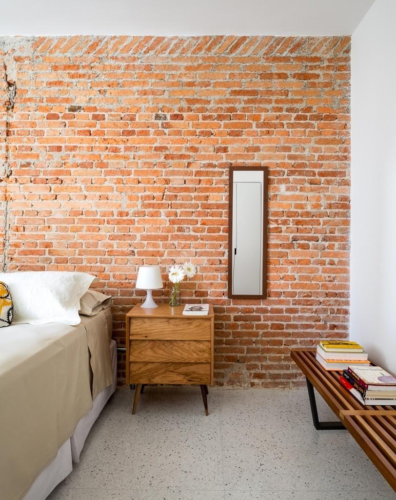 O quarto tem parede descascada que exibe a alvenaria original da construção. O criado-mudo e o espelho com ares