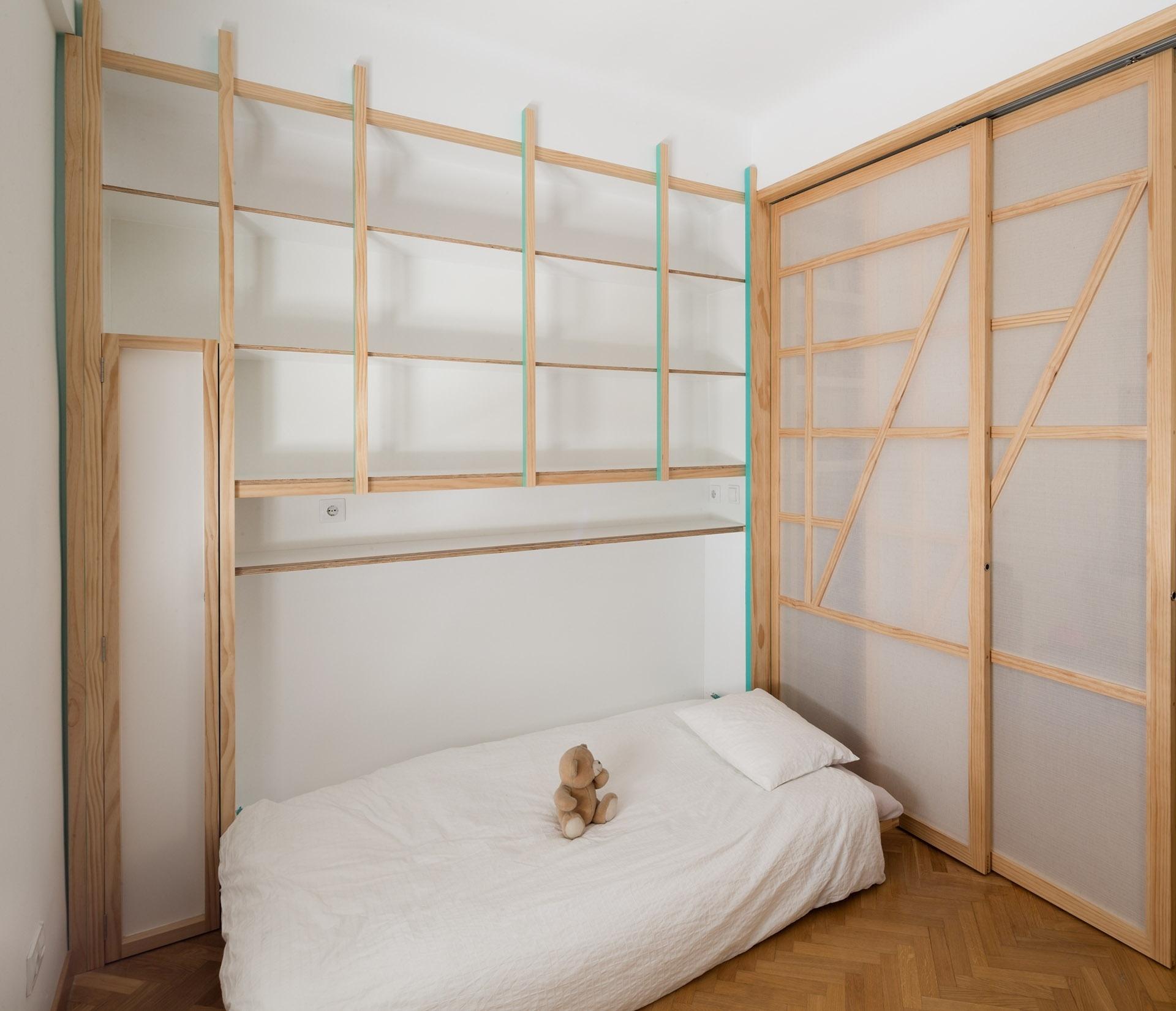 A marcenaria de uma das paredes embute uma cama para hóspedes. O quarto, que parece vazio, conta com móveis embutidos intitulados