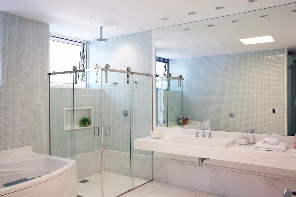 O banheiro da suíte máster é revestido com pastilhas cerâmicas e mármore. Ao lado do boxe de vidro com roldanas na parte superior está uma convidativa banheira. O projeto da casa, que fica no condomínio Bauhaus, é da arquiteta Monica Drucker