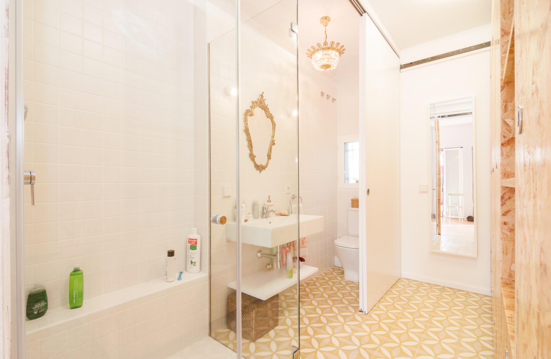 O banheiro é um dos poucos cômodos fixos da residência em função da rede hidráulica. No ambiente, a decoração busca harmonia com a padronagem do OSB (que dá forma aos módulos móveis), pelo uso de revestimentos claros e poucos (mas expressivos) adornos. O projeto faz parte da série Pequeñas Grandes Casas desenvolvida pelos arquitetos do escritório PKMN, em Madri