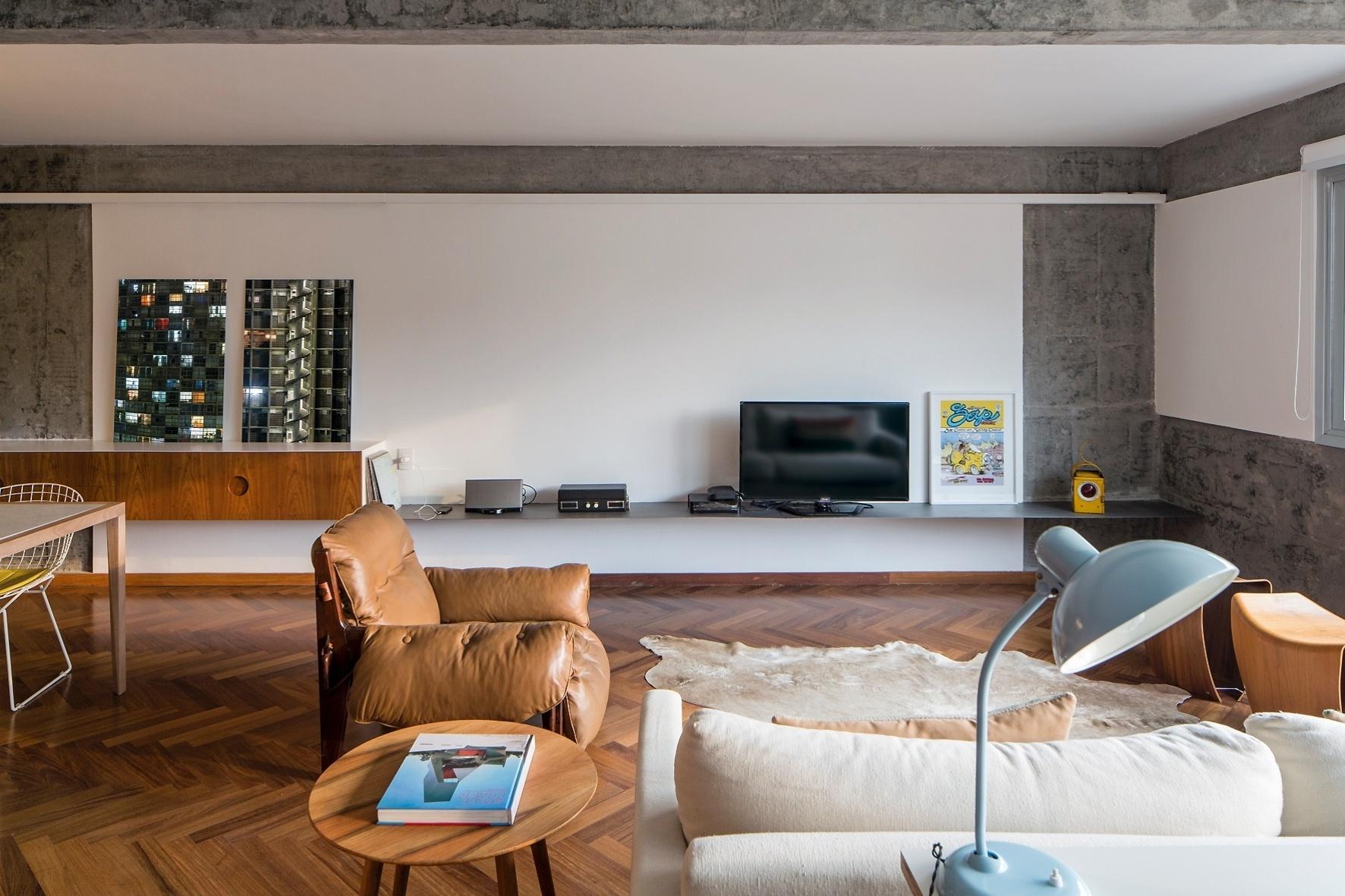Completamente reformado, o Apartamento FT fica em um edifício construído nos anos 50 e teve o piso renovado com madeira sucupira (ParquetSP). Na parede ao fundo, a chapa de aço-carbono crua, delgada e leve serve de base para a TV e outros equipamentos, dobrando-se à esquerda, onde emoldura o aparador. A ideia dos projetistas do escritório Pascali Semerdjian era encaixar a marcenaria (Marvelar) nos módulos metálicos com acabamento mais leve