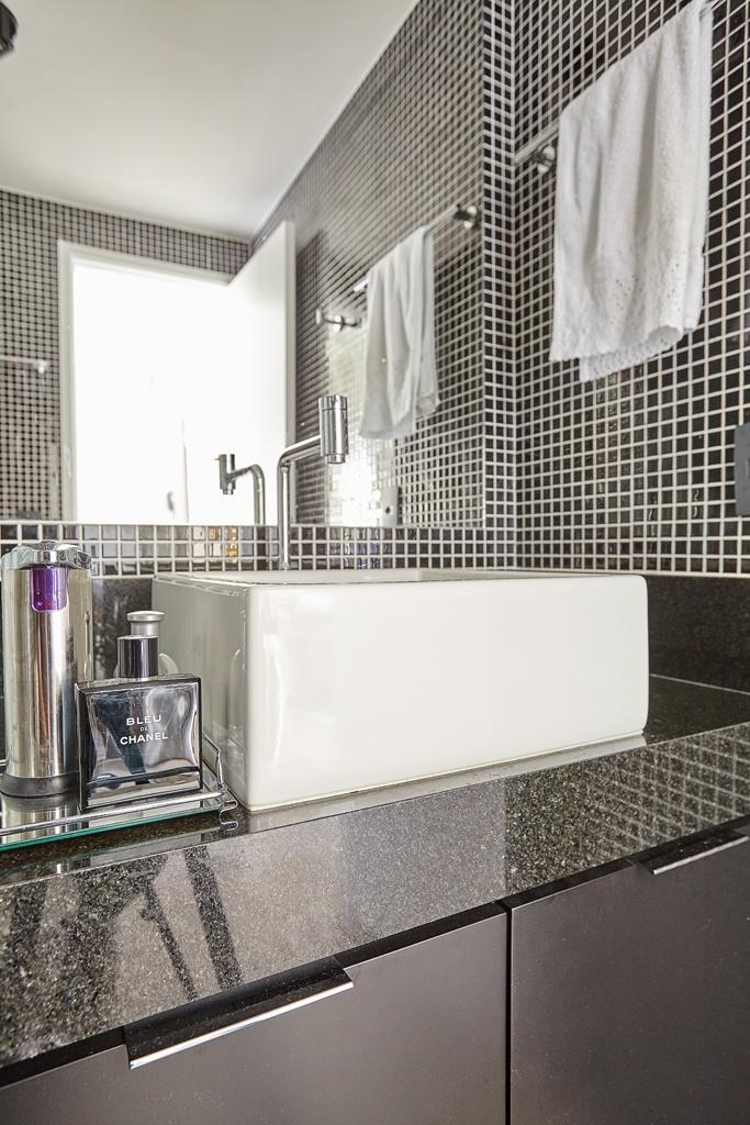 No banheiro, o lavatório é composto de bancada de granito e cuba de apoio e tem, sob si, o gabinete suspenso que racionaliza o espaço. O estúdio em Pinheiros, São Paulo, foi projetado pelo escritório Notar Design