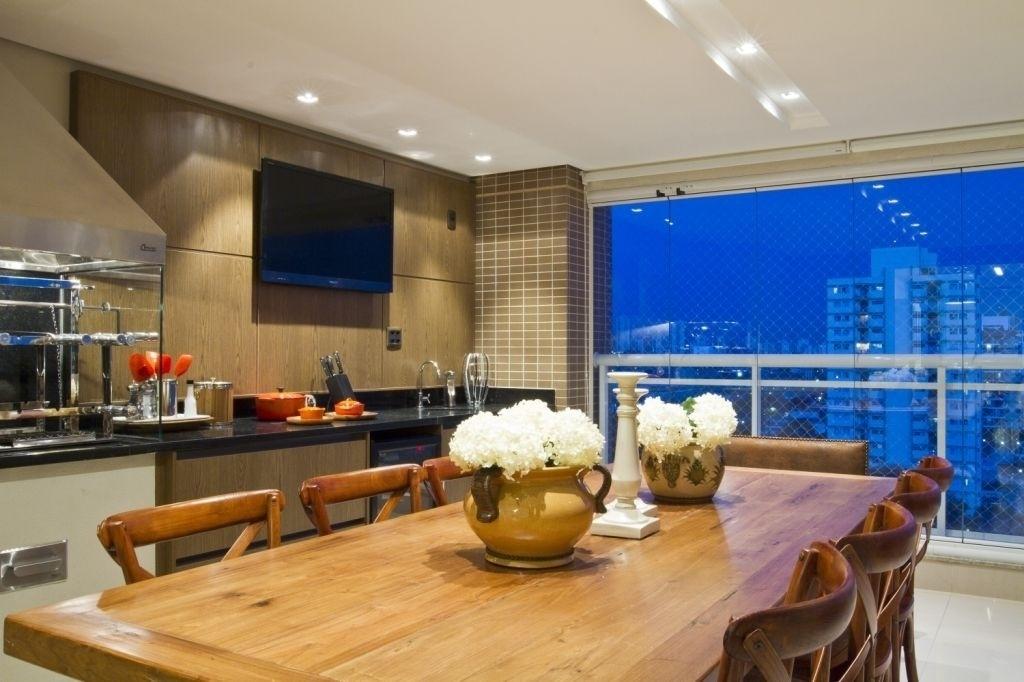 A varanda gourmet projetada pela arquiteta Camila Klein é bastante ampla e confortável, ideal para reunir a família em momentos de lazer. O espaço conta com churrasqueira, TV, uma extensa bancada e uma mesa com dez lugares
