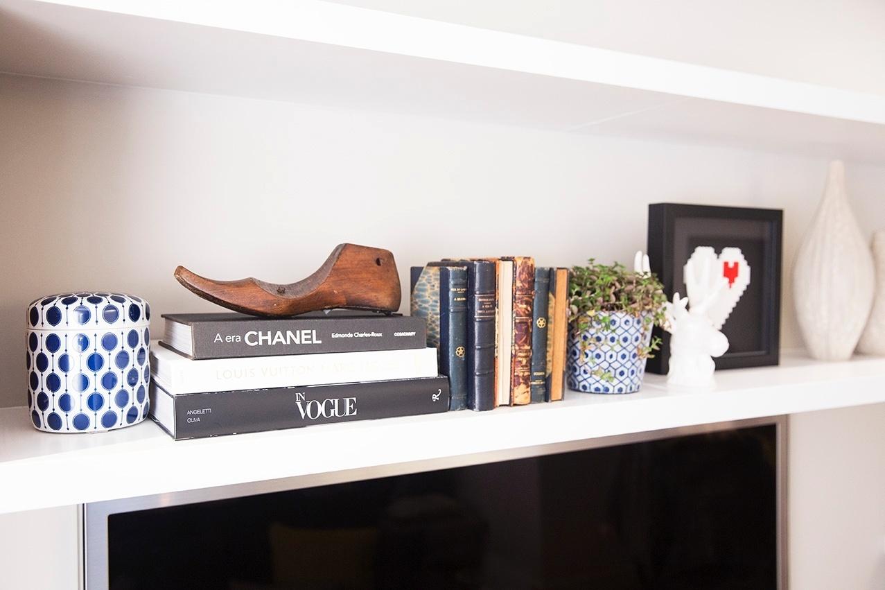 No home theater estão peças decorativas, livros antigos e lembranças de viagem da coleção do casal. Sobre alguns volumes, uma forma de sapateiro. O projeto de interiores é do escritório DN2 Arquitetura