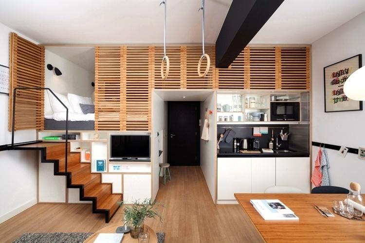 Para abrir espaço para os ambientes sociais, as funções íntimas (quarto, banheiro e armazenamento) são empilhadas em um único módulo no loft Zoku. Na parte superior, a área de dormir é acessada por uma escada retrátil (à esq.) e está encoberta por uma porta feita de ripas de madeira, que garante a privacidade. Abaixo da cama, ficam escondidos o guarda-roupa e as gavetas, além da TV embutida. O projeto de interiores é assinado pelo escritório de arquitetura holandês Concrete
