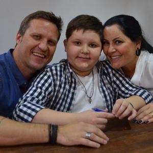 O menino Thor com os pais, Rafael e Claudia, no lançamento do livro