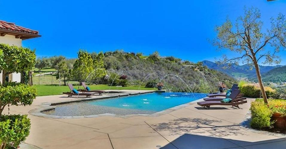 A piscina da mansão de Britney Spears é decorada com cinco espreguiçadeira em redor de sua borda. Mini jatos de água caem no tanque, que tem vista para as montanhas. A residência está à venda por R$ 32 milhões, na Califórnia, Estados Unidos