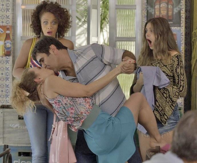 Kátia (Aline Borges) e Cassandra (Juliana Paiva) assistem, atônitas, ao surto de Hugo (Orã Figueiredo), que rouba um beijo de Lurdinha (Carolyna Aguiar) em