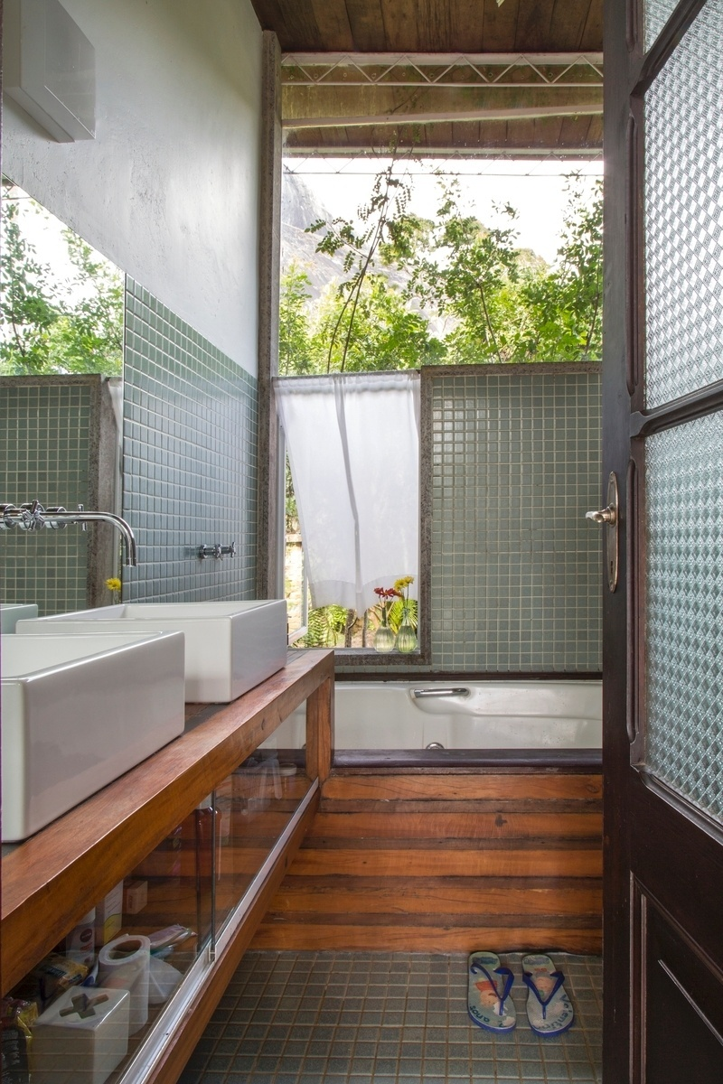 O banheiro da suíte master tem vista para a paisagem e bancada de madeira acoplada à banheira. A casa Samambaia tem projeto do arquiteto Rodrigo Simão