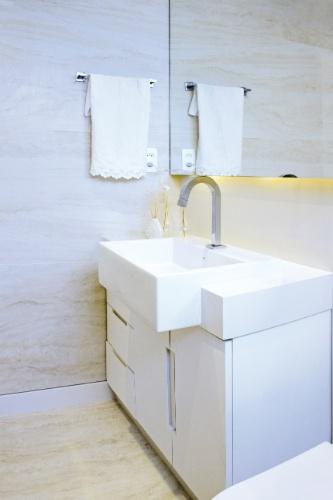 No banheiro da suíte, a bancada é feita de superfície cristalizada de vidro polido com cuba embutida. O armário laqueado foi executado sob medida e a parede foi revestida de porcelanato no padrão Travertino. A reforma do apê em Botafogo, Rio de Janeiro, é do escritório Ravaglia & Philot Arquitetura